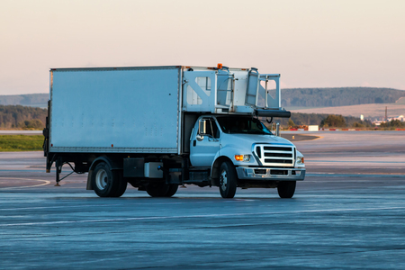 Truck delivering food to the airplane at the airport apron Фото со стока