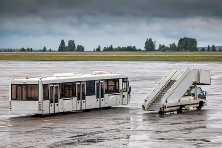Shuttle bus and passenger boarding stairs at the airport apron in a rainy day
