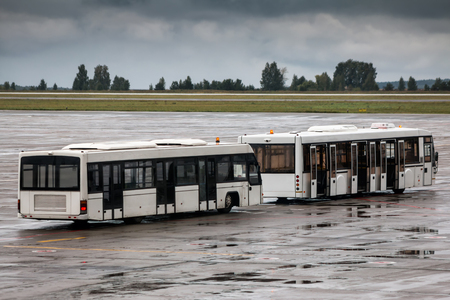 Two empty shuttle buses at the airport apron in a rainy day Фото со стока