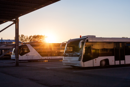 Shuttle buses at the parking lot of the airport in the rays of the setting sun Фото со стока - 100282816