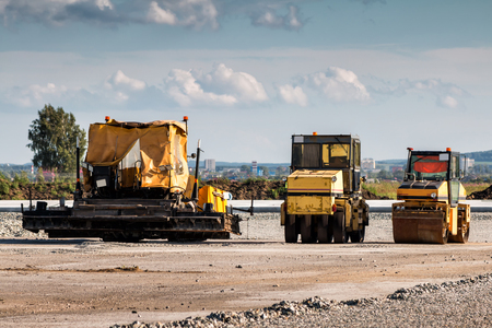 Asphalt paver and two tandem rollers for road repair