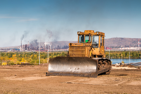 Yellow bulldozer against the backdrop of an industrial landscape Фото со стока - 101353630