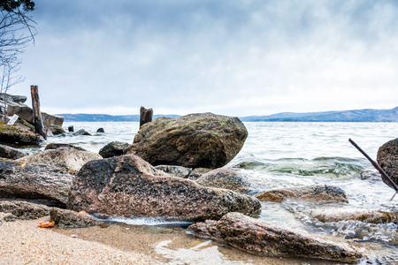 Large blocks of stones on the shore of the lake on a cloudy day