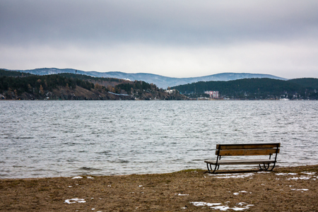 Bench on the lake shore on a winter day