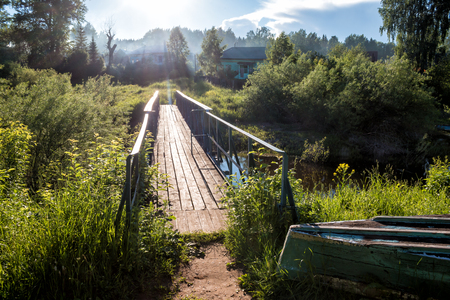 A bridge across a small river in the village in the sun rays Фото со стока - 103833634
