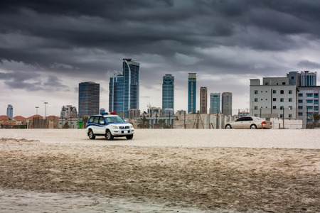 Police off-road car and city sedan on a sandy beach in the background of skyscrapers in cloudy weather