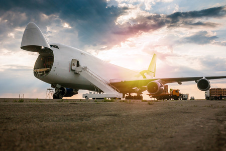Unloading wide body transport cargo plane in the morning sun Фото со стока - 104791744