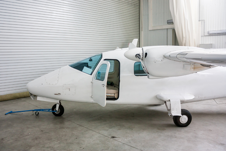 High-winged twin-engined light aircraft with open door in hangar Фото со стока - 106432961
