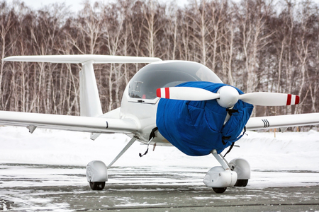 Close-up shrouded small sports airplane at winter