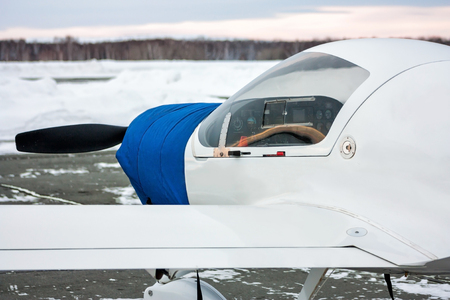 Close-up front of the shrouded small sports aircraft at winter