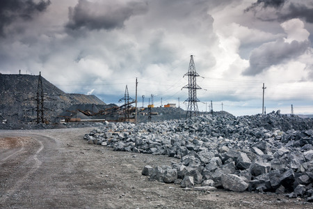 Stone dumps, power lines and crushing machines in a quarry in cloudy weather