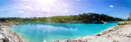 Panorama of a scenic flooded clay quarry with turquoise water in the morning sun Фото со стока - 106567111