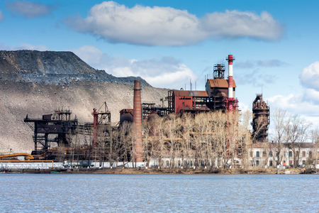 Industrial plant near the lake against the backdrop of a huge dump