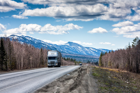 A long-distance truck with a semitrailer moves on the road among the mountains covered with snow