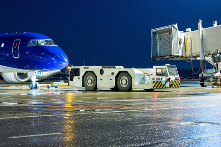 The tow tractor rolls back the passenger airplane from the air bridge at the night airport apron Фото со стока