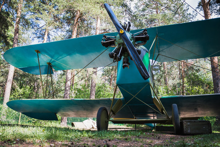 Old retro biplane on a forest aerodrome