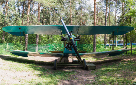 Old vintage biplane on a forest airfield Фото со стока