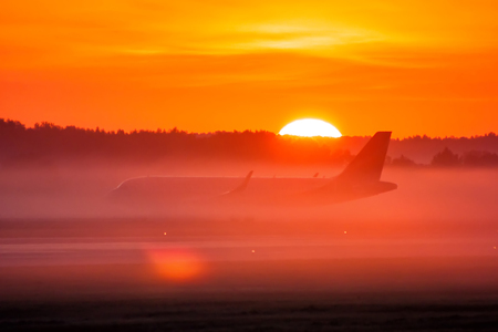 Taxiing a passenger airplane in the fog and sunrise Фото со стока - 109390457