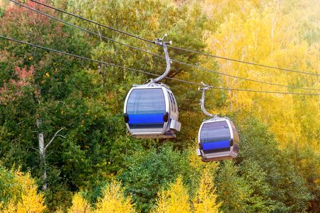 Aerial lift to the mountain in the autumn forest Фото со стока