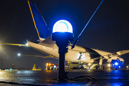 Taxiway, side row lights on the background of a large passenger aircraft at the night airport apron