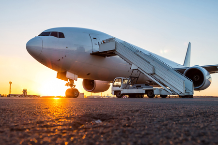 White wide body passenger airplane with a boarding stairs at the airport apron in the evening sun