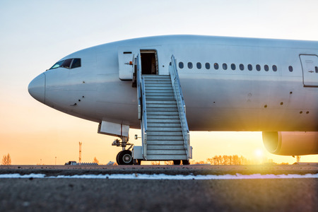 White wide-body passenger aircraft with a boarding steps at the airport apron in the evening sun