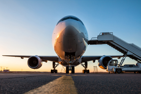 Front view of white wide body passenger airplane with a boarding stairs at the airport apron in the evening sun