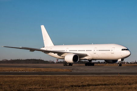 White wide body passenger aircraft taxiing on the main taxiway Фото со стока
