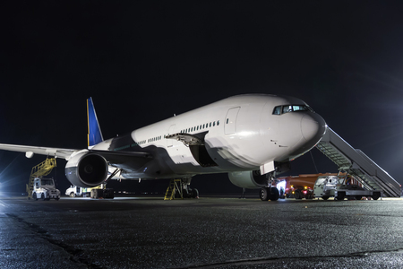 Wide-body passenger aircraft with air-stairs at the night airport apron. Airplane ground handling