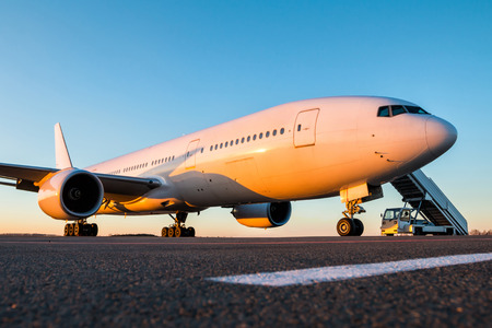 White wide-body passenger aircraft with air-stairs at the airport apron in the evening sun Фото со стока