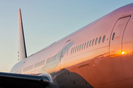 Close-up of the fuselage of a white passenger airplane in the evening sun Фото со стока