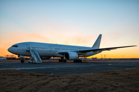 White wide body passenger airplane with boarding steps at the airport apron in evening twilight