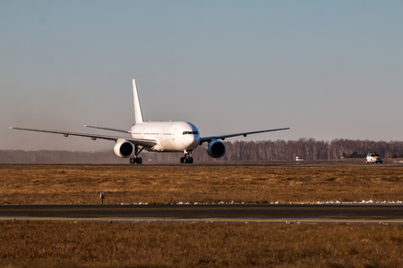 White wide body passenger airplane moves behind the Follow-me-Car on the main taxiway