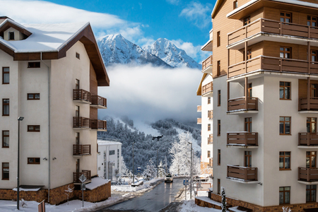 Multi-storey buildings with views of high mountain peaks on a clear sunny day in winter