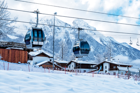Gondola lifts, village and high mountain range on a clear sunny day in winter