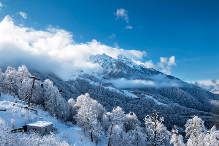 Snowy peaks of mountains above the clouds and gondola lift on a clear winter day