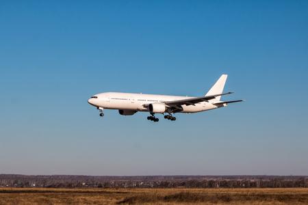 Landing white wide-body passenger aircraft