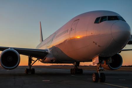 Weiße Großraum-Passagierflugzeuge auf dem Flughafenvorfeld in der Abendsonne