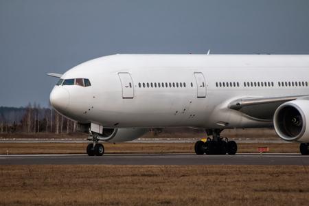Close-up taxiing white wide body passenger airplane Фото со стока