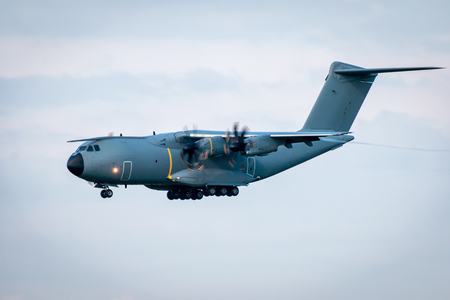 Landing heavy military transport turboprop aircraft Stock Photo