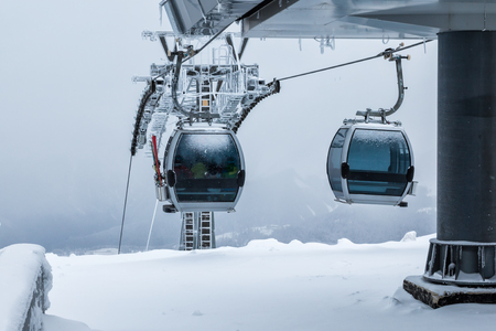 Gondola lifts on top of the mountain in winter Фото со стока