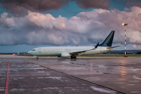 Taxiing a passenger aircraft on the airport apron on an overcast evening after rain Фото со стока