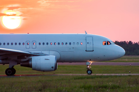 Close-up taxiing a white passenger airplane against the setting sun Фото со стока