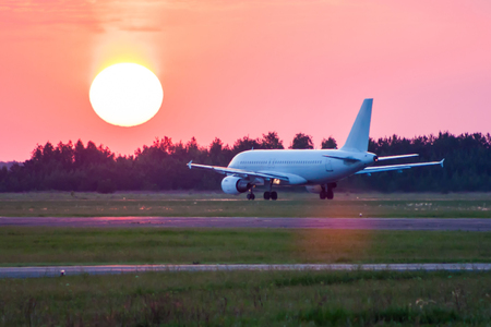 White passenger aircraft on the runway towards the setting sun