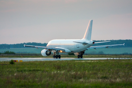White passenger airplane taxiing to the runway