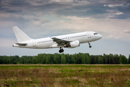 White passenger aircraft in the air on take-off Фото со стока