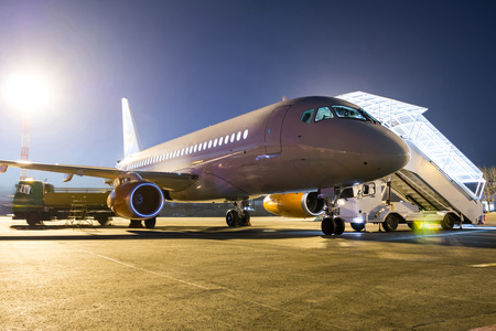 White passenger jet plane with boarding steps at the night airport apron Фото со стока