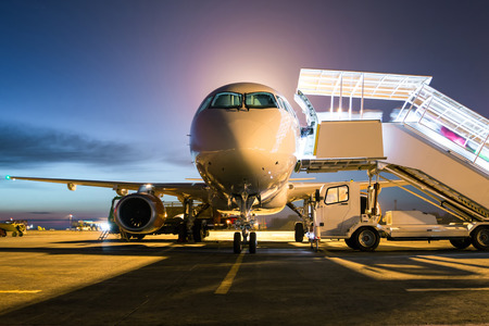 Front view ground handling of white passenger airplane with a boarding steps at the night airport apron