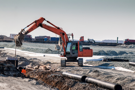 Orange excavator and other special equipment at road construction