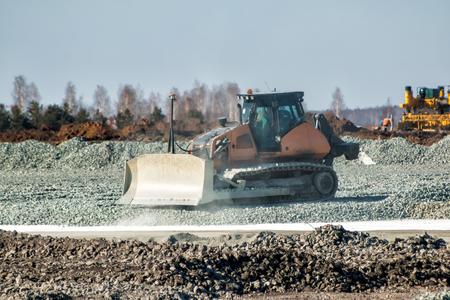 Bulldozer dredges rubble on road construction